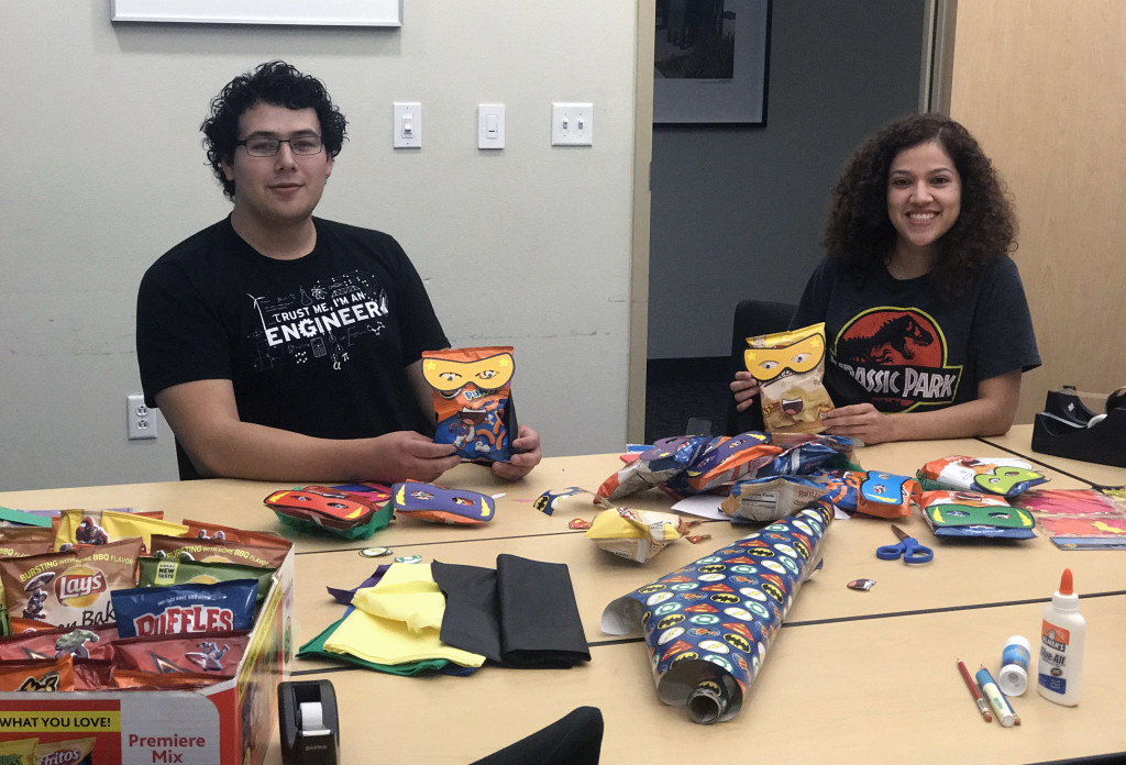 Employees decorate bags of chips in the McAllen office conference room.